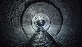 Diggers,Are,Exploring,Underground,River,Flowing,In,Round,Sewer,Tunnel